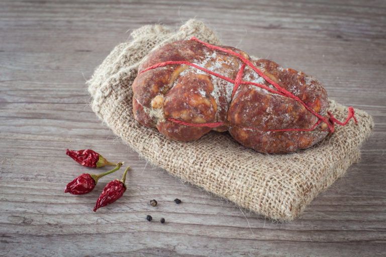 Tasty italian Soppressata ham on wooden background